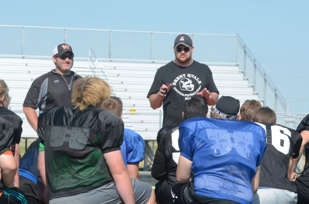 Brent Qvale, WHS graduate, talks to participants at his football camp this summer in Williston. Photo credit: Williston Herald.