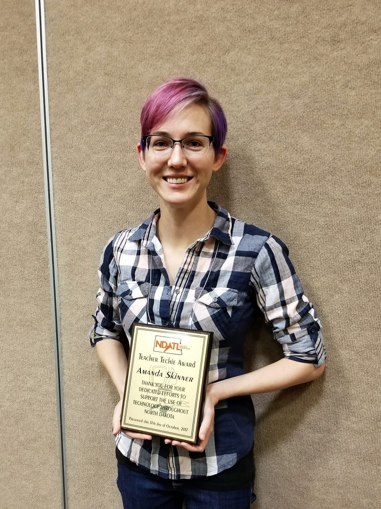 Amanda Skinner, WHS teacher with purple hair, glasses, and a flannel, holds her teacher of the year award and smiles.