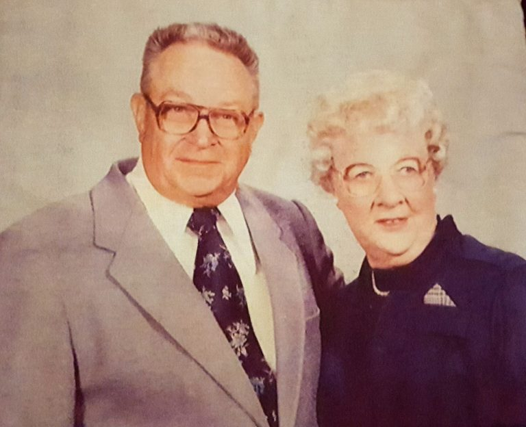 Ted and his wife, Lois Schmitz. Two smiling, older Caucasian people. Both have white hair and thin, wire-frame glasses. The man is in a white shirt and the woman in a light blue jacket.